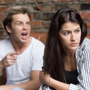 Man skriker och pekar finger, kvinna vänder bort blicken och ser frustrerad ut