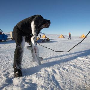 En person sågar igenom isen i Antarktis.