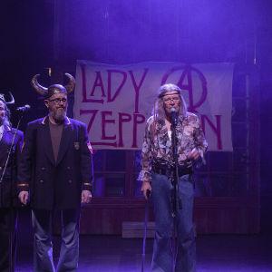 Kuvassa on meneillään bänditreenit. Lady Zeppelin -julisteen edessä laulaa mikkiin Heikki Kinnusen näyttelmä Marja-Terttu Zeppelin.