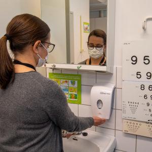 En skolhälsovårdare i munskydd står och tvättar händerna.