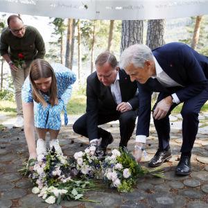 Tre människor lägger ner blommor under minnesceremoni för Utøya.