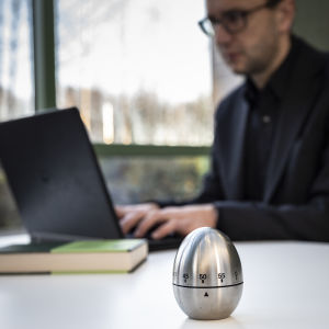 munakello pöydällä kertomassa kuinka pitkään tehdä töitä läppärillä
