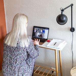 Läraren Susanne Ojaniemi undervisar sin klass via en dator på distans i sit them. Hon har datorn på ett skrivbord av trä och svart lampa syns bredvid bordet där Ojaniemi sitter.