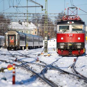 Tåg på rad på snöig tågdepå.