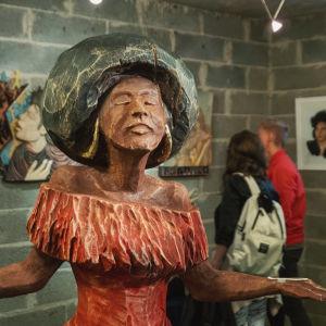 Laulaja Diana Rossia kuvaava puuveistos, taustalla näkyy muutama ihminen ja muita puutaideteoksia.