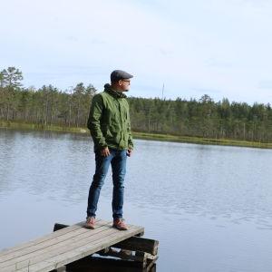 En man med grön jacka och keps står på en liten brygga vid en insjö i Lauhanvuori nationalpark.