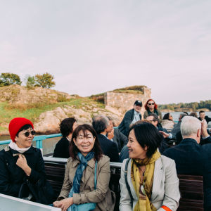 People sitting down on the outside deck of a ferry boat. Suomenlinna in the background.