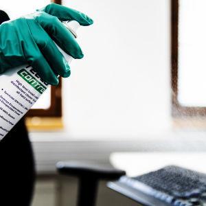 Kuvassa suihkutetaan desinfiointiainetta tietokoneen päälle.