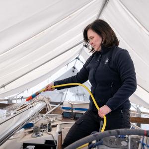 Nora Boijer-Spoof pesemässä 38-jalkaisen purjeveneen kantta, Verkkosaaren telakka, Helsinki, 4.4.2020.