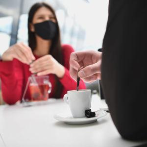 Kvinna i munskydd och man som bara syns bakifrån sitter på café
