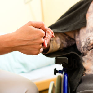 En ung kvinnas hand som håller i en äldre kvinnas hand. Den yngre kvinnan är iklädd vita sjukhuskläder och den äldre kvinnan sitter i rullstol.