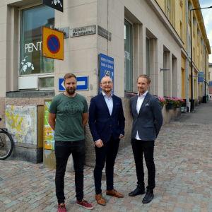 Tre män framför Valtimohuset.