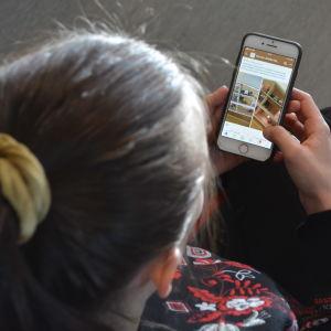 Henkilö selaa älypuhelimesta nettikirpputoria.