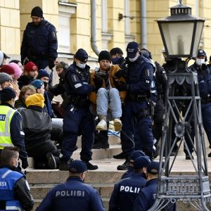 Polisen flyttar på en demonstrant utanför ett stenhus under en demonstration.