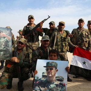 Syriska regeringsstyrkor poserar för en bild. Som rekvisita har de Syriens flagga och bilder på Bashar al Assad.