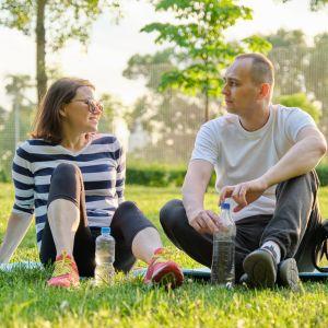 Man och kvinna sitter på gräsmatta och ser på varandra