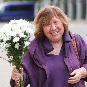 Kvinna klädd i lila står med vit blombukett i handen.