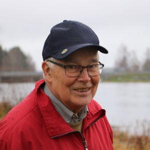 En äldre man med blå keps står intill en å.