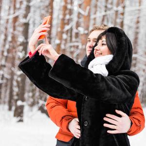 Ett par tar en selfie i en snöig omgivning.
