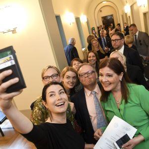 De grönas Emma Kari tar en selfie med sina riksdagskolleger.