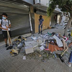 Personer städar gatan efter explosionen i Beirut.