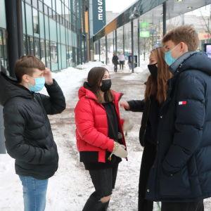 Fyra ungdomar står utanför ett köpcenter och pratar.