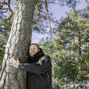 Jonas Forsbacka står och kramar ett träd ute i skogen på Emsalö. Jonas har en ängslig min, och skogen syns i bakgrunden.