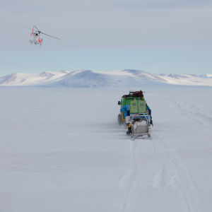 En helikopter flyger över isen i Antarktis.