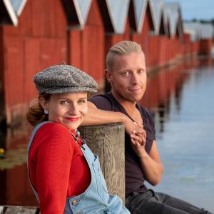 Juontajat Hannamari Hoikkala ja Nicke Aldén istuvat järven äärellä laiturilla, taustalla punamullattuja kalamajoja.