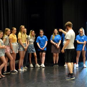 Flickor i shorts och t-skjorta står i en halvcirkel och en man står framför dem