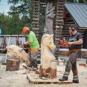 Mies sahaa moottorisahalla puusta hevosen muotoista veistosta, taustalla toinen sahaaja