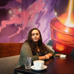 En kvinna sitter vid ett bord på ett café. Hon ser allvarlig ut.