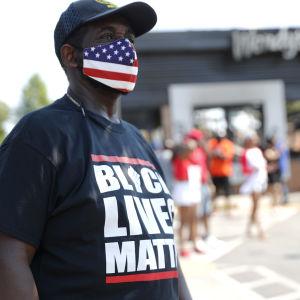En svart man med ett munskydd i den amerikanska flaggans färger. På mannens skjorta kan man läsa texten Black lives matter.