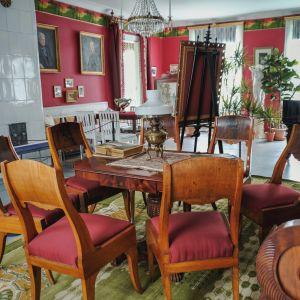 kuva salista, jossa vanhanaikaisia huonekaluja, taustalla kakluuni ja flyygeli