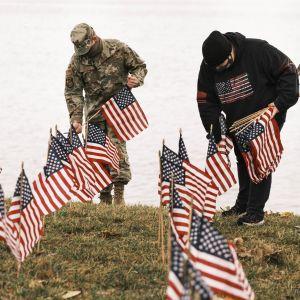 Kaksi miestä pystyttää USA:n lippuja rannalle.