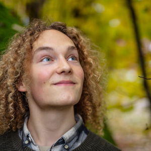 Porträtt på en ung man med lockigt, halvlångt rödbrunt hår.