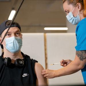 Ung vuxen man vaccineras mot coronavirus av en sköterska.