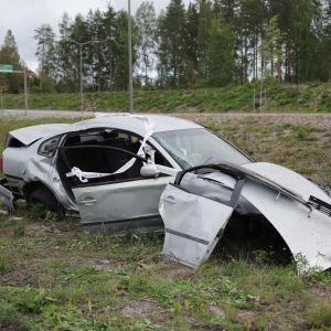Ulosajossa vaurioitunut auto tien vieressä.