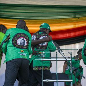 Säkerhetsmän för folk i säkerhet efter en explosion vid ett valmöte i Zimbabwe