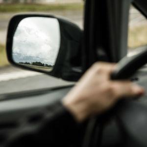 Backspegel och hand på bilratt