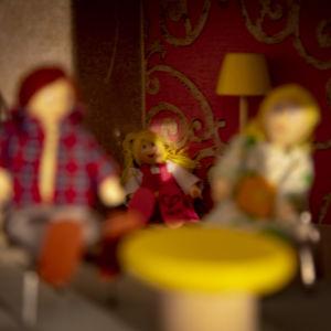 En liten flickdocka sitter i ett rött dockhus. Bredvid henne sitter en mammadocka och en pappadocka.