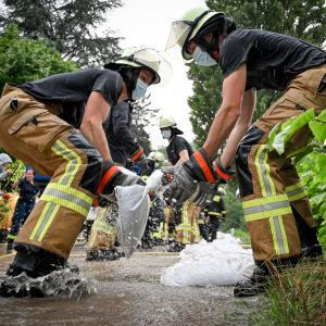 Räddningsarbetare försöker stoppa översvämningarna med att bygga rader med sandsäckar.