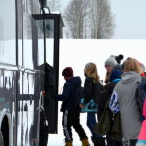 Elever stiger på buss.