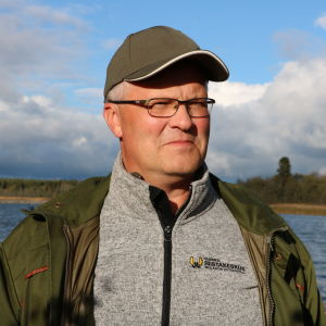 En medelålders man med keps och glasögon står framför havet. Han är iklädd en grön jacka och grå fleece-tröja med texten Finlands viltcentral skrivet på vänstra bröstet.