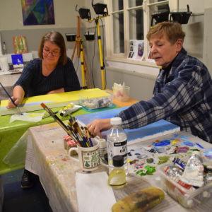 Susanne Kollin och Helena Lähteenmäki målar tavlor.