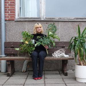 Tia Hassinen sitter på en bänk utanför Strömborgska skolan, med två plantor i handen.