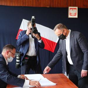 Andrzej Duda äänestää maski kasvoillaan.