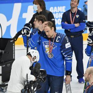 Suomen kapteeni Marko Anttila haroi hiuksiaan hopeamitali kaulassa.
