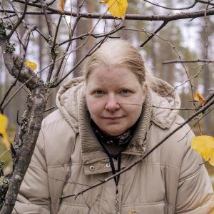 Mirkku Salo katsoo kameraa keltaisten lehtien ja koivun oksien seasta.