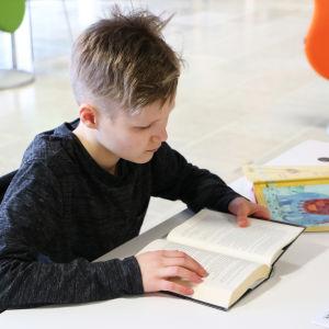 En pojke sitter och läser i en bok.